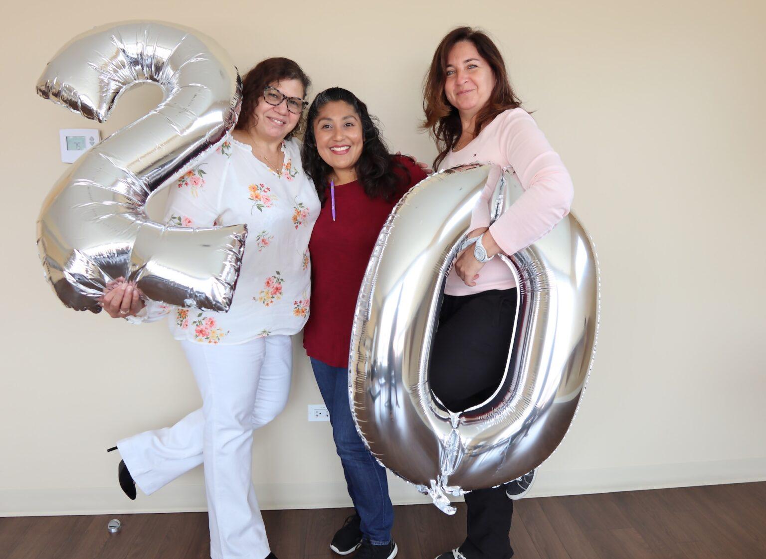 Three women holding up balloon 20